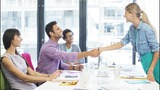 Business people shaking hands in meeting.