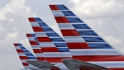 This July 17, 2015, file photo shows the tails of four American Airlines passenger planes parked at Miami International Airport, in Miami. (AP Photo/Alan Diaz, File)