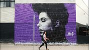 A woman walks past a Prince mural on April 28, 2016 in Sydney, Australia.