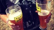 A festival-goer holds two glasses of beer at the 2014 Wacken Open Air heavy metal music festival on on August 1, 2014 in Wacken, Germany.