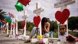 A woman writes a note on a cross at a memorial outside the Orlando Regional Medical Center on June 17, 2016.