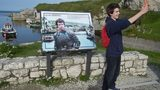 A Game of Thrones fan takes a 'selfie' beside a plaque at Ballintoy Harbour on August 13, 2015 in Belfast, Northern Ireland.