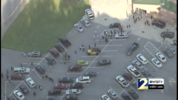 Students at Lithia Springs High School are seen walking through the parking lot and back into the school building after an incident in which a teacher shot himself, police said.