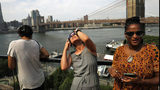 People watch a partial solar eclipse from the roof deck at the 1 Hotel Brooklyn Bridge on August 21, 2017 in the Brooklyn borough of New York City.