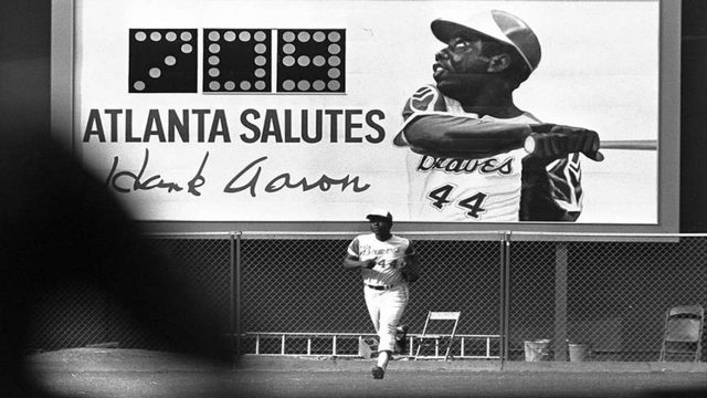 An Electronic Sign Showing The Number Of Hank Aarons Home Runs Provides A Background As Aaron Off Field After Eighth Inning First Game