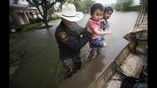 Fort Bend County Sheriff Troy Nehls and Lucas Wu lift Ethan Wu into an airboat as they are evacuated from rising waters from Tropical Storm Harvey, at the Orchard Lakes subdivision on Sunday, Aug. 27, 2017, in unincorporated Fort Bend County, Texas.