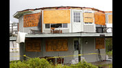 A house on Sullivan's Island shows its windows covered in preparation for Tropical Storm Irma hit Sullivan's Island, S.C., Monday, Sept. 11, 2017. The house, however, lost its roof after the storm went through the area. The names on the cardboard are of other named storms that the house had survived, the house owner said. (AP Photo/Mic Smith)