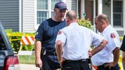 In this Tuesday, Sept. 19, 2017 photo, investigators in Bloomington, Ill., speak outside a home where they believe a fire that left a man and two children dead was intentionally set.