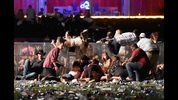 People scramble for shelter at the Route 91 Harvest country music festival after apparent gun fire was heard on October 1, 2017 in Las Vegas. Police have confirmed that one suspect has been shot. The investigation is ongoing. (David Becker/Getty)