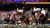 People scramble for shelter at the Route 91 Harvest country music festival after apparent gun fire was heard on October 1, 2017 in Las Vegas, Nevada.