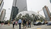 Pedestrians walk past a recently built trio of geodesic domes that are part of the Seattle headquarters for Amazon, on Sept. 7, 2017.