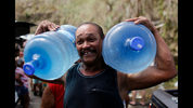 A man carries two water jugs filled with water near San Juan.