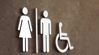 Pizza shop owner removes bathroom signs after protests