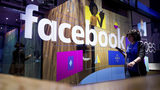 FILE - In this Tuesday, April 18, 2017, file photo, a conference worker passes a demo booth at Facebook's annual F8 developer conference in San Jose, Calif. Facebook Inc. reports earnings Wednesday, Nov. 1, 2017. (AP Photo/Noah Berger, File)