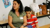 In this Tuesday, Nov. 14, 2017, photo, recent transplant from Puerto Rico, Arieliss Valencia sits next to her son Anthony, right, a fifth grader at Riverdale Elementary School after school supplies were handed out to the students in Orlando, Fla.