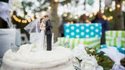 Bride and groom cake topper on cake (stock photo)