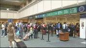 Passengers wait to go through security at Orlando International Airport.