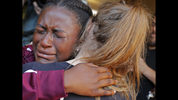 Marla Eveillard, 14, cries as she hugs friends before the start of a vigil at the Parkland Baptist Church, for the victims of Wednesday's shooting at the Marjory Stoneman Douglas High School in Parkland, Fla. (AP Photo/Gerald Herbert)