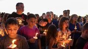 People attend a candlelit memorial service Thursay night for the victims of the shooting at Marjory Stoneman Douglas High School that killed 17 people.