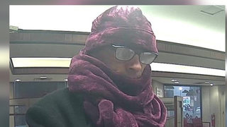 Thief creates spectacle, robbing bank in dress, purple scarf and hat