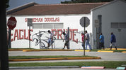People sweep the grounds for evidence as law enforcement officials continue to investigate the scene at Marjory Stoneman Douglas High School on February 19, 2018 in Parkland, Florida.