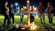 People visit one of seventeen crosses following a candlelight vigil for the victims of the shooting at Marjory Stoneman Douglas High School in Parkland on Feb. 15. Gov.