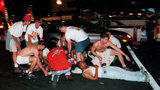 Spectators tend to injured victims following an early morning explosion in Atlanta's Olympic Centennial Park Saturday, July 27, 1996. The explosion killed a woman and injured more than 100 other people