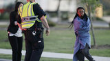 An employee wrapped in a blanket talks to a police officer after she was evacuated at a FedEx distribution center where a package exploded, Tuesday, March 20, 2018, in Schertz, Texas.
