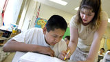 Teacher Blanca Feliciano assists a student in her sixth-grade class during summer school July 2, 2003 in Chicago, Illinois.