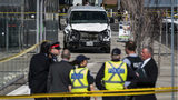 Toronto police officials stand near the damaged van that was used to run down pedestrians on a city street April 23, 2018. (Aaron Vincent Elkaim/The Canadian Press via AP)