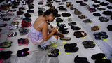 A woman places one of the hundreds of shoes in memory of those killed by Hurricane Maria in front of the Puerto Rico Capitol, in San Juan, Friday, June 1, 2018. Puerto Rico's Institute of Statistics announced that it has sued the U.S. territory's