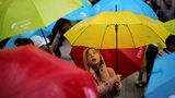 Young children dance with their umbrellas at the launch of an art installation called the Umbrella Project, featuring 200 brightly colored umbrellas suspended over Church Alley on June 22, 2017 in Liverpool, England.