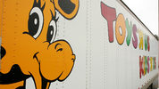 Geoffrey the Giraffe is seen on the side of a Toys 'R' Us truck. The statue that stood in the headquarters of the toy store company has a new home in a children's hospital lobby.