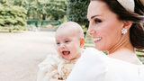 In this Monday, July 9, 2018 photo made available by Kensington Palace, Kate, the Duchess of Cambridge poses for a photo with Prince Louis in the garden of Clarence House, following Prince Louis's baptism at the Chapel Royal, St. James's Palace.