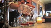 A bartender pours a pair of cocktails at The Courtesy Bar in Orlando.