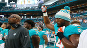 Miami Dolphins defensive end Robert Quinn raises his right fist during the singing of the national anthem before Thursday night's preseason game.