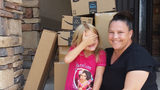 Catherine Lunt and her daughter, 6-year-old Katelyn, pose with a stack of Amazon boxes full of toys Katelyn ordered without her mom's permission.