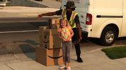 Katelyn Lunt, 6, poses with the delivery driver who delivered over $350 worth of toys Lunt secretly purchased using her mom's Amazon account.