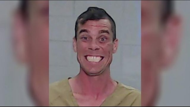 Man accused of robbing thrift store smiles in mugshot after