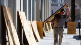 Preston Guiher carries a sheet of plywood as he prepares to board up a Wells Fargo bank in preparation for Hurricane Florence in downtown Charleston, S.C., Tuesday, Sept. 11, 2018.