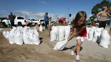 Chloe Heeden, 4, from Virginia Beach, Va., drags a sandbag to her father's car, Wednesday, Sept. 12, 2018, in Virginia Beach, Va., as Hurricane Florence moves towards the eastern shore.