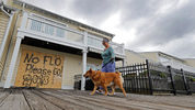 Barbara Timberlake walks with her dog Danny past a boarded up store on the river front in downtown Wilmington, N.C., as Hurricane Florence threatens the coast Thursday, Sept. 13, 2018.