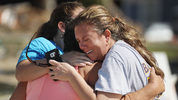 Elizabeth Hanson (R) and her daughter, Emaly Hanson, hug neighbor Cindy Clark after dealing with their homes that were heavily damaged when Michael passed through the area on October 11, 2018 in Mexico Beach, Fla.  (Photo: Joe Raedle/Getty Images)