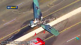 This photo taken from video provided by KABC-TV shows a vintage North American AT-6 airplane that crashed on U.S. 101 in Agoura Hills, Calif., Tuesday, Oct. 23, 2018. The pilot escaped uninjured and no one on the ground was hurt.