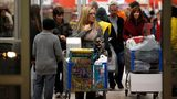 Customers leave Walmart with their purchased items Thanksgiving day on Nov. 28, 2013, in Troy, Michigan.