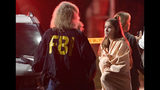 An FBI agent talks to a potential witness as they stand near the scene Thursday, Nov. 8, 2018, in Thousand Oaks, Calif. where a gunman opened fire Wednesday inside a country dance bar, wounding 11 people including a deputy who rushed to the scene.
