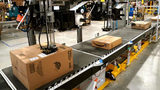 A machine applies shipping labels to packed orders at an Amazon fulfillment center.
