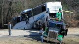 Employees from a wrecker service work to remove a charter bus from a roadside ditch Monday, Dec. 3, 2018, after it crashed alongside Interstate 30 near Benton, Ark.