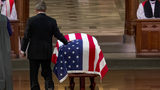 Former President George Bush touches the flag-draped casket of his father, former President George H.W. Bush, as he prepares to speak during his State Funeral at the National Cathedral, Wednesday, Dec. 5, 2018. (AP Photo/Andrew Harnik, Pool)