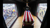 The flag-draped casket of former President George H.W. Bush passes through Magnolia, Texas, Thursday, Dec. 6, 2018, along the route from Spring to College Station, Texas. (AP Photo/David J. Phillip, Pool)